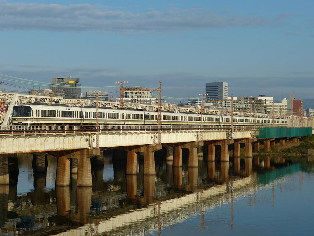朝陽を浴びて上淀川鉄橋を渡る221系12連
