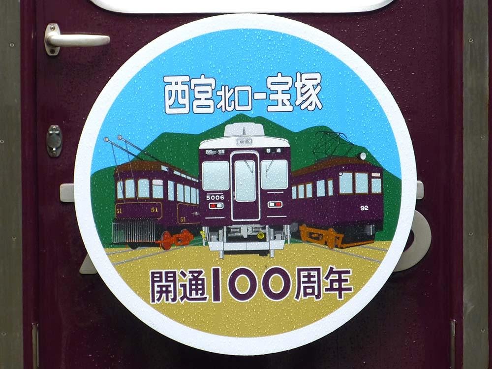 阪急今津線「西宮北口~宝塚駅間」開通100周年記念ヘッドマーク(西宮北口側に掲出)。51形、5000系、90形のイラストが掲載されています。